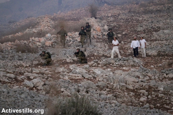 Israeli soldiers accompany Israeli settlers as settlers carry out vigilante attacks against local Palestinians and their land in the West Bank village of Bur'in, October 3, 2015. (Ahmad Al-Bazz/Activestills.org)