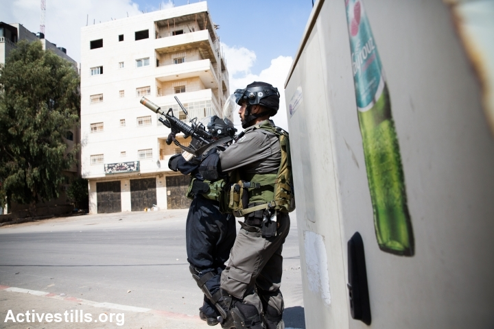 Israeli border policeman shoots in the air during clashes with Israeli forces near the illegal settlement of Beit-El, West-Bank, on October 8, 2015. Tension rises in the past weeks in the region with reciprocal violent attacks of both Israelis and Palestinians and clashes around the West Bank, Jerusalem and Palestinian towns in Israel. (photo: Yotam Ronen/Activestills.org)