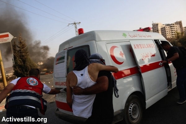 A Palestinian youth is carried to an ambulance during clashes at the DCO checkpoint in the West Bank, October 5, 2015 (Muhannad Saleem/Activestills)