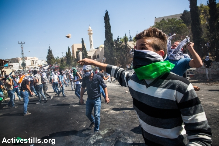 Palestinian protesters throw stones during clashes with Israeli forces in the neighbourhood of Abu Dis, east Jerusalem, October 11, 2015. (photo: Yotam Ronen/Activestills.org)