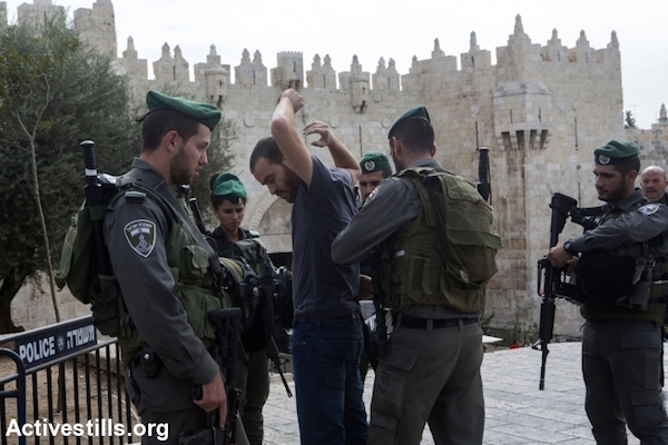 Israeli Border Police search a Palestinian man near Damascus Gate in the Old City of Jerusalem, October 23, 2015. Many new checkpoints have been set up in East Jerusalem's Palestinian neighborhoods in the wake of a spate of stabbings in the city. Jerusalem, October 23, 2015. (Anne Paq/Activestills)