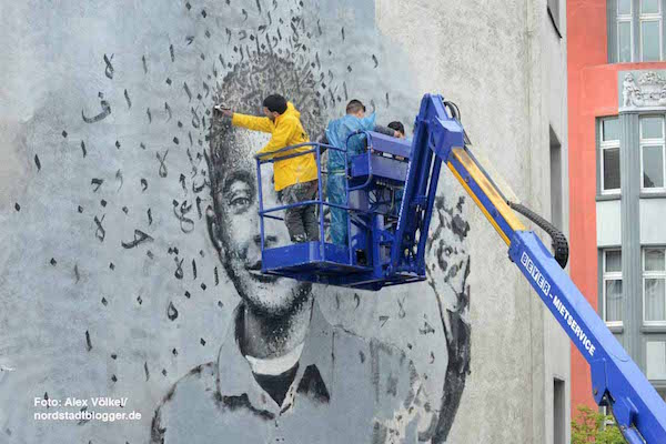 Yazan Halwani, joined by local students, working on the mural of Fares in Dortmund, Germany. (Photo by Alex Volkel)
