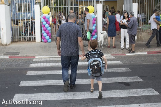 Illustrative photo of a parent bringing his child to school in Jaffa, Israel. (Oren Ziv/Activestills.org)