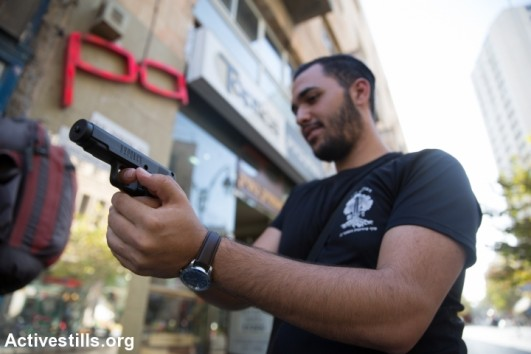 Israeli shows a tear gas gun he just bought at a gun shop in Jerusalem on October 15, 2015. Arms shop's owners report a rise in demand for wepons and other self deface gear as violance continues around Jerusalem. (photo: Yotam Ronen)