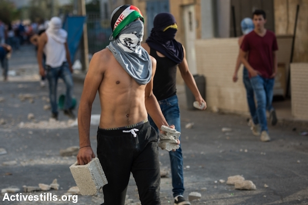 A Palestinian youth prepares to throw pieces of concrete during clashes in the East Jerusalem neighborhood of Shuafat, October 5, 2015. (Faiz Abu Rmeleh/Activestills.org)