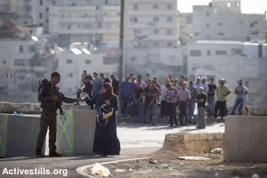 An Israeli Border Police officer stops and inspects Palestinians trying to leave their East Jerusalem neighborhood of Issawiya, October 15, 2015. (Oren Ziv/Activestills.org)