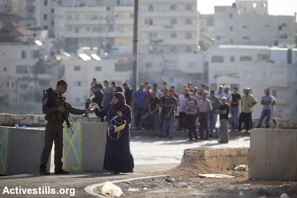 An Israeli Border Police officer stops and inspects Palestinians trying to leave their East Jerusalem neighborhood of Issawiya, October 15, 2015. Police erected checkpoints at the entrances and exits of almost all Palestinian neighborhoods of Jerusalem, a form of collective punishment following a spate of stabbing attacks. (Oren Ziv/Activestills.org)