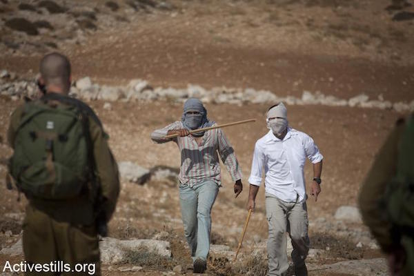 File photo of masked Israeli settlers threatening Palestinians while soldiers look on. (Oren Ziv/Activestills.org)