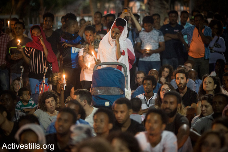 Members of the Eritrean community in Israel hold a memorial service for a memorial ceremony for asylum seeker Habtom Zarhum in Levinsky park in south Tel Aviv, October 21, 2015. Zarhum died after he was shot by an Israeli security guard at a bus station in the southern city of Beersheba where he was mistaken for an assailant in an attack that killed an Israeli soldier. Zarhum, who was kicked by an angry mob after being shot will not be recognized as an official victim of terrorism. (Oren Ziv/Activestills.org)