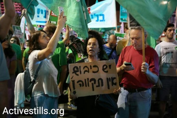 A woman holds a sign reading: 'With occupation, there is no hope,' during a protest march against the Netanyahu government, Tel Aviv, October 24, 2015. (Yotam Ronen/Activestills.org)