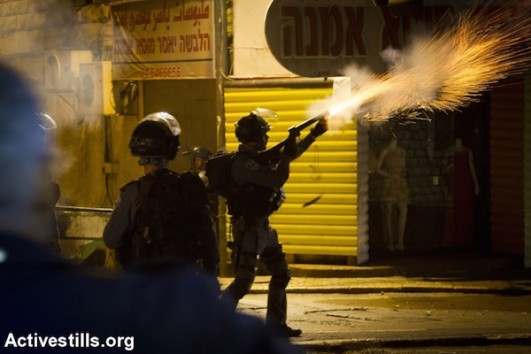 A special forces policeman fires tear gas at protesters during clashes between Israeli Police and Palestinians at a protest calling to protect Al-Aqsa Mosque in Nazareth, October 8, 2015. (Omar Sameer/Activestills)