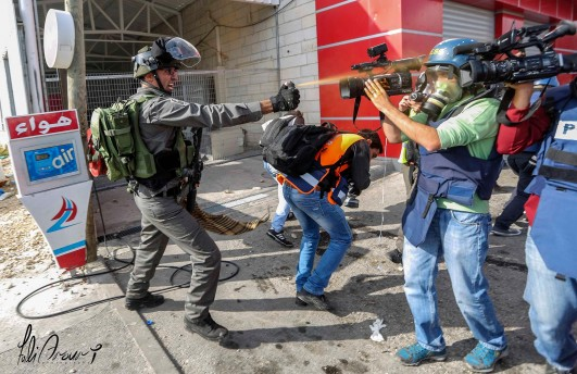 A member of Israel's Border Police assaults journalists and medics assembled near Al Bireh, West Bank (credit: Fadi Arouri)