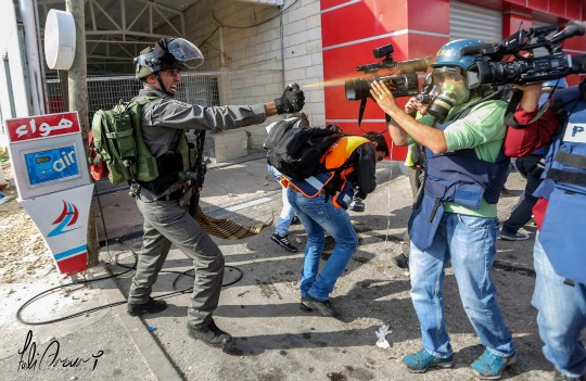 A member of Israel's Border Police assaults journalists and medics assembled October 30 near Al Bireh, West Bank (credit: Fadi Arouri)