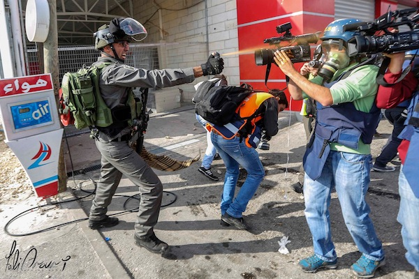 A member of Israel's Border Police assaults journalists and medics assembled near Al Bireh, West Bank (photo: Fadi Arouri)