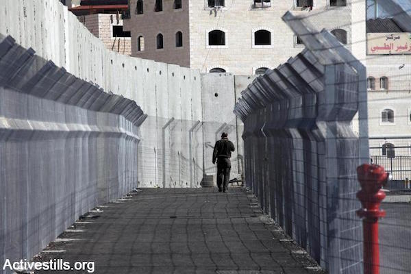 A Palestinian resident of East Jerusalem walks into a checkpoint that separates the entirely walled-off neighborhood of Shuafat Refugee Camp, East Jerusalem, December 27, 2011. (Anne Paq/Activestills.org)