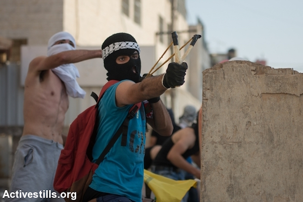 A Palestinian youth uses a sling-shot to shoot stones at Israeli police during clashes in the East Jerusalem neighborhood of Shuafat, October 5, 2015. (Faiz Abu Rmeleh/Activestills.org)