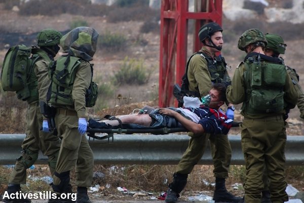 Israeli army medics carry away a young Palestinian stone thrower who was shot in the leg by undercover Israeli troops on the outskirts of Ramallah. A tourniquet can be seen on his leg where he was shot, October 7, 2015. (Muhannad Saleem/Activestills.org)