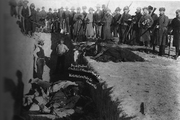 U.S. soldiers throw the bodies of massacred Lakota Indians into a mass grave, following the massacre at Wounded Knee Creek, South Dakota.