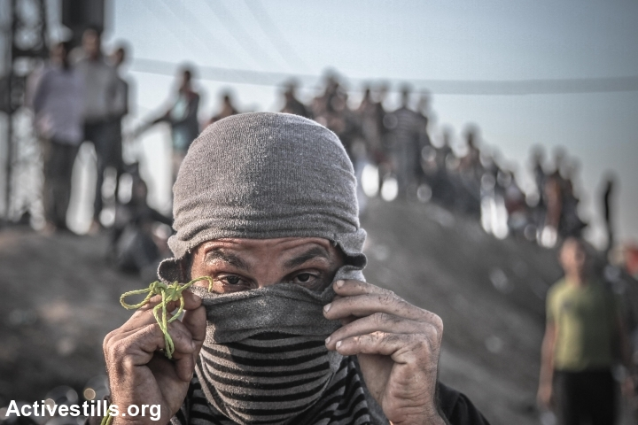 A Palestinian man adjusts his mask during a protest near the Gaza Strip's border with Israel, October 30, 2015. (photo: Ezz Zanoun/Activesills.org)