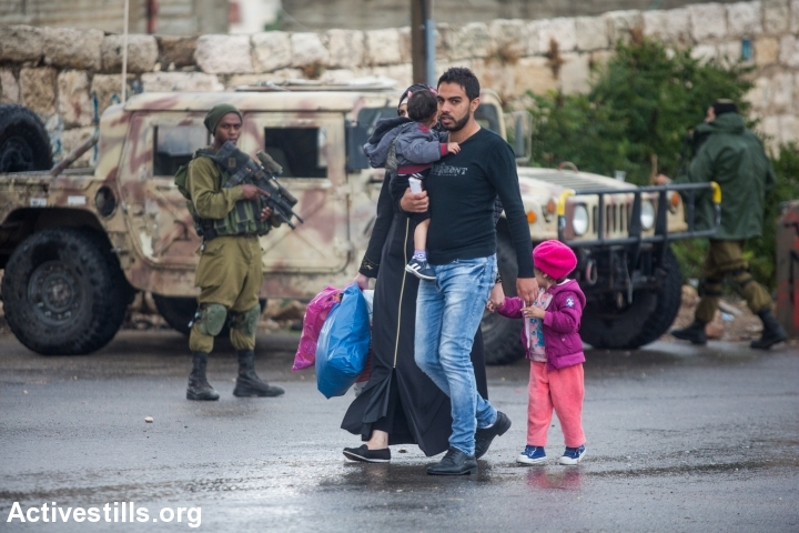 Israeli soldiers watch as a Palestinian family walks down a street in the occupied city of Hebron, West Bank, October 29, 2015. (photo: Yotam Ronen/Activestills.org)