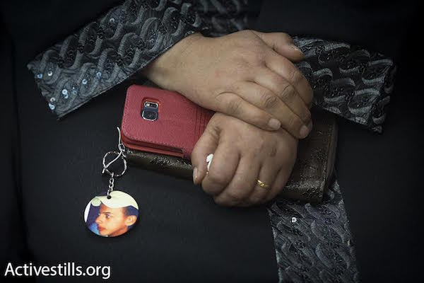 Suha, the mother of Palestinian teenager Muhammad Abu Khdeir, who was murdered last year, clasps a phone with a photo keyring of her son as she sits in the district court in Jerusalem on November 30, 2015. (Oren Ziv/Activestills)