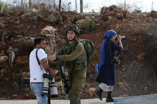 Alla Badarna being pushed back by a soldier as an Israeli photographer is allowed to work without any hindrance. (Photo by Ayman Nubani)