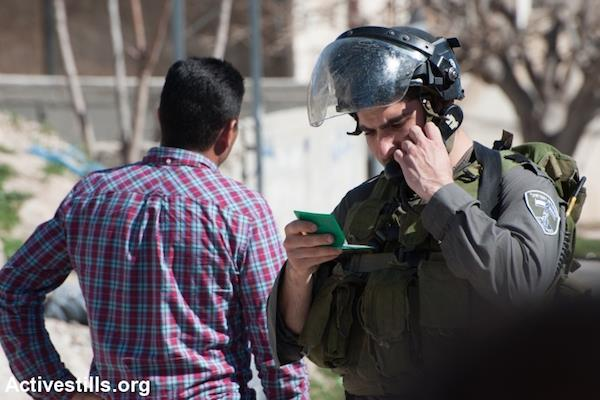An Israeli soldier checks a Palestinian man's identity card. Israel controls the Palestinian population database and issues green ID cards to Palestinians whereas Israelis receive blue cards. (Photo by Activestills.org)