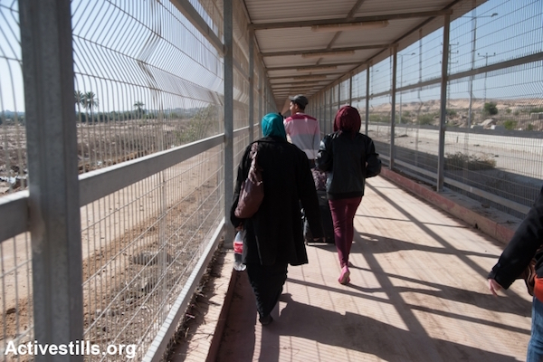 "Palestinians walk through the kilometer-long path through the ""no-go zone"" separating Israel's Erez crossing and Beit Hanoun in the Gaza Strip, December 18, 2013. (Ryan Rodrick Beiler/Activestills.org)"