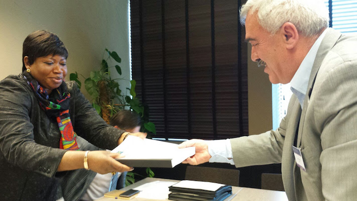 Al-Haq director Shawan Jabarin hands the confidential communication, complied by four Palestinian human rights organizations, to ICC Prosecutor Fatou Bensouda in the Hague, November 23, 2015. (Photo courtesy of Al-Haq)