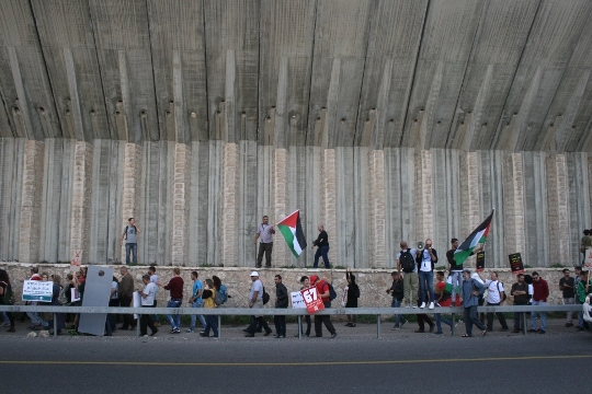 Anti-occupation protesters march along the side of Route 60 in the West Bank, against the backdrop of a massive concrete barrier erected by Israel, November 27, 2015. (Haggai Matar)