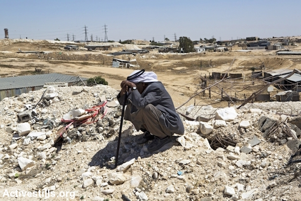 A man from the Zanoun family sits on the ruins of his house a few hours after it was demolished by the Israeli Land Administration, in the unrecognized bedouin village of Wadi Al Na'am, Negev Desert, May 18, 2014. (Keren Manor/Activestills)