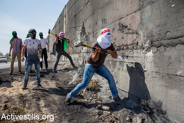 Palestinian protesters trying to brake a section in the Separation Wall, during clashes with Israeli forces in the neighbourhood of Abu Dis, east Jerusalem, October 11, 2015. Tensions rise in recent weeks with violent attacks by both Israelis and Palestinians and clashes around the West Bank, Jerusalem and Palestinian towns inside Israel. 17 Palestinians have been killed since Oct. 1 to 10, while four Israelis, including two settlers, have been killed in the same time period. (Activestills.org)