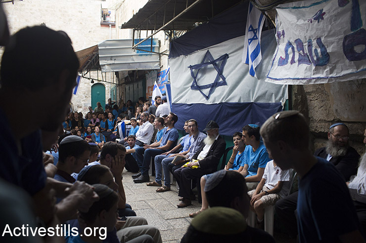 Israeli settlers pray on site where two Israelis were killed in a stabbing attack last week, in Jerusalem's old city, October 12, 2015. Israeli police blocked Al wad street in Jerusalem's old city, to allow Israeli settlers to pray at the sit of a stabbing attack that took place last week. (Activestills.org)