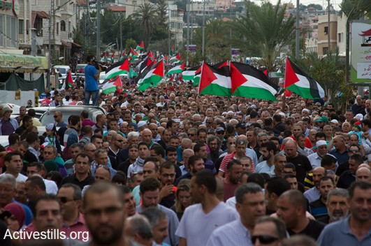 Palestinians with Israeli citizenship, some holding Palestinian flags, take part in a large protest during a general strike in solidarity with Palestinians in Jerusalem, West Bank and Gaza, in the northern town of Sakhnin, on October 13, 2015. Palestinians call for a Day of Rage following restrictions on Al Aqsa and recent violent attacks of both Israelis and Palestinians. (Activestills.org)