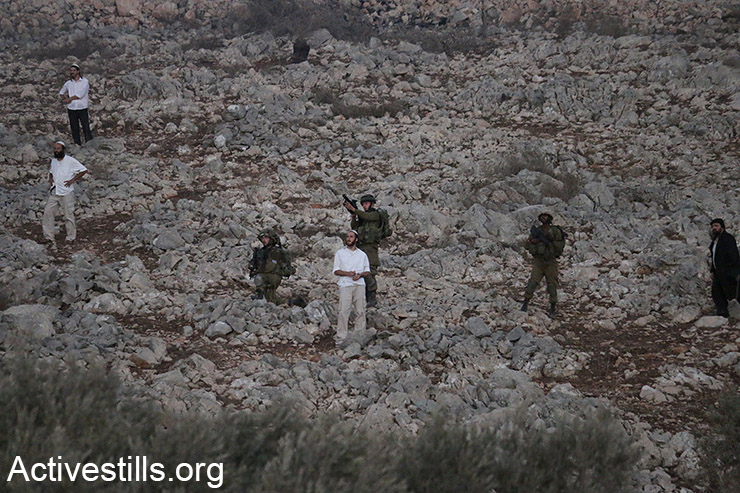 Israeli settlers stand near Israeli soldiers during clashes erupted after the former set fire to Palestinian agricultural fields in Burin village near Nablus, as tensions remain high in the West Bank following the killing of two settlers and reprisal attacks on Palestinian villages, October 3, 2015. (Activestills.org)