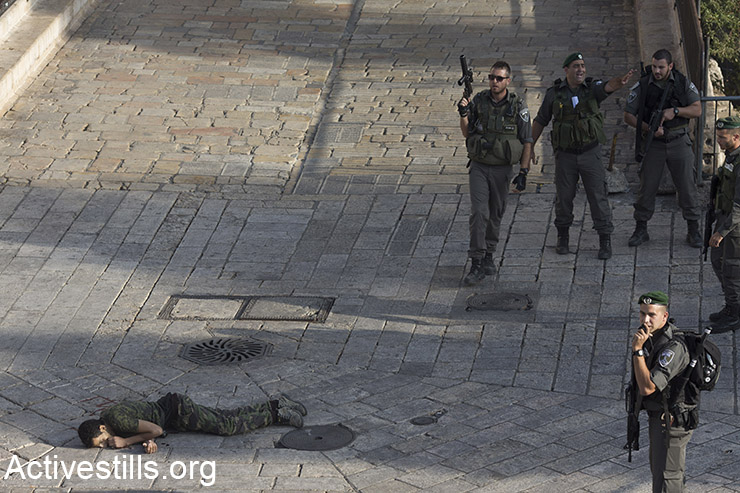Israeli police stand around a Palestinian shot after he allegedly tried to stab a person at Damascus Gate, Jerusalem's Old City, October 14, 2015. (Activestills.org)