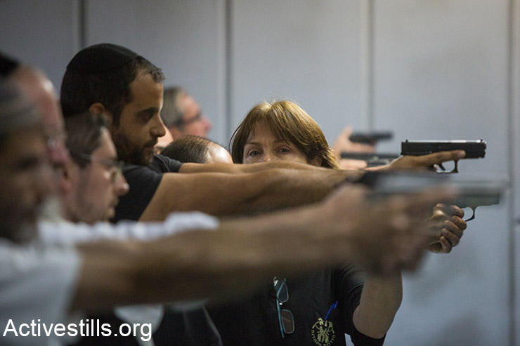 Israelis attend a shooting practice in a gun shop in Jerusalem on October 15, 2015. Arms shop's owners report a rise in demand for weapons and other self defence gear as violence continues around Jerusalem. (Activestills.org)