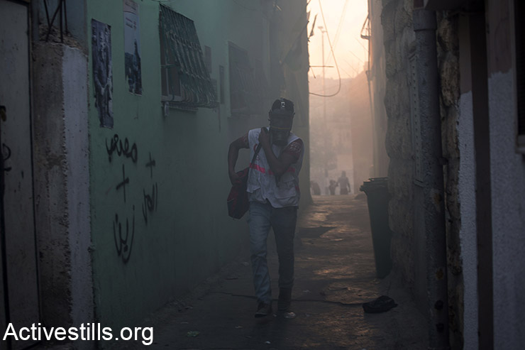 A Palestinian medic walks through tear gas in the narrow alleys of al-Azzeh refugee camp, during clashes between Palestinians youths and the Israeli army, in Bethlehem, October 15, 2015. Tensions rise in recent weeks with violent attacks by both Israelis and Palestinians and clashes around the West Bank, Jerusalem and Palestinian towns inside Israel. At least 35 Palestinians have been killed in the occupied Palestinian Territories since Oct.1, while seven Israeli have been killed. More than 1,100 Palestinians were injured and 600 arrested in the same period. (Activestills.org)