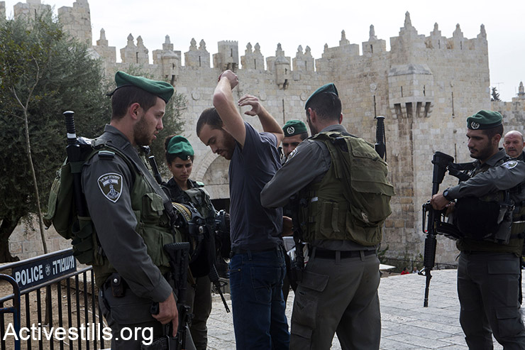 Israeli policemen search a Palestinian man near Damascus Gate, in the Old city of Jerusalem, October 23, 2015. Many new checkpoints have been set up in the Palestinian quarters of Jerusalem. Tensions rise in recent weeks with violent attacks by both Israelis and Palestinians and clashes around the West Bank, the Gaza Strip, Jerusalem and Palestinian towns inside Israel. (Activestills.org)