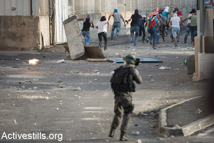 Palestinian youth run from Israeli police during clashes in Sh'uafat neighbourhood in East Jerusalem, October 5, 2015. Violence in the occupied West Bank and Jerusalem has intensified in the past few weeks. (Activestills.org)