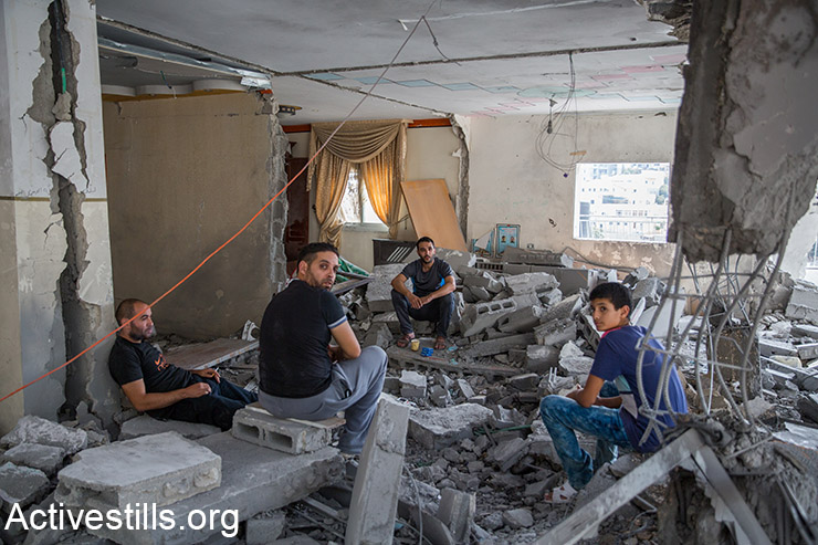 Palestinians from the Abu Jaber family sit on the ruins of their home that was demolished by Israeli forces, East Jerusalem, October 6, 2015. The house belonged to the family of Ghassan Abu Jaber, who killed four worshippers in an attack on a synagogue last year. (Activestills.org)