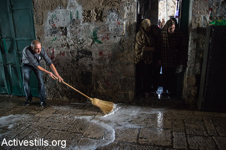 A Palestinian man cleans the scene where a Palestinian woman allegedly tried to stabbed an Israeli man, following which she was shot to death, Jerusalem's Old City, October 7, 2015. (Activestills.org)