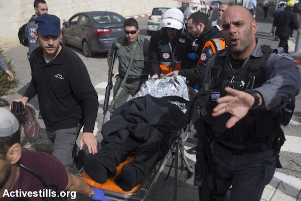 An Israeli tramway security guard, stabbed by two Palestinian boys, is wheeled away on a stretcher at the scene of the assault at a tramway station in the settlement neighborhood of Pisgat Ze'ev in annexed East Jerusalem on November 10, 2015. One of the Palestinian boys, a minor, was shot and wounded while the other was arrested. The security guard was wounded and taken to hospital. (photo: Activestills.org)