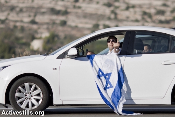 An Israeli driver makes an obscene gesture toward a joint Palestinian-Israeli demonstration against the occupation and violence, Road 60, West Bank, November 27, 2015. (Mustafa Bader/Activestills.org)