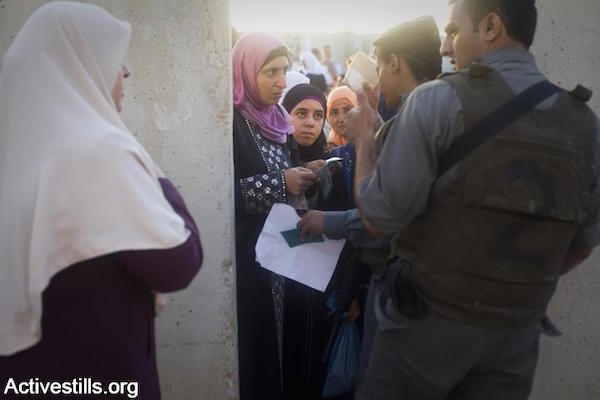 Israeli soldiers check Muslim Palestinian women's IDs as thousands try to pass through the Qalandiya checkpoint on the last Friday during Ramadan, September 3, 2010. Harsh restrictions by the Israeli army meant that many who attempted to pass were turned away, while others waited for a long time at the checkpoint in Ramallah. (Photo: Oren Ziv/Activestills)