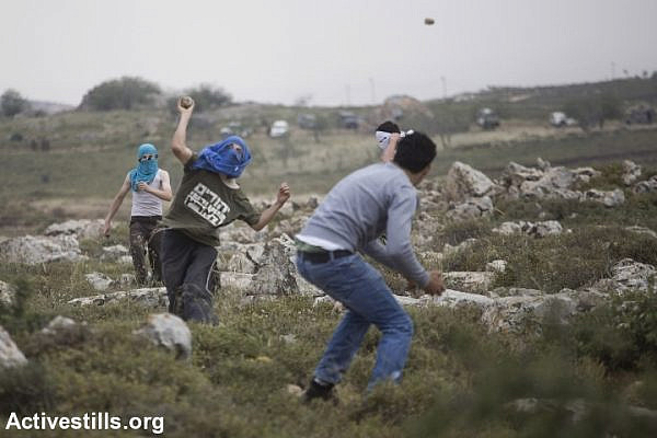 Israeli settlers and Palestinian demonstrators throw stones at each other, after settlers marched onto the lands of the West Bank villages of Deir Jarir and Silwad where villages were protesting the construction on their land by members of the nearby Jewish settlement of Ofra, May 3, 2013. (photo: Oren Ziv/Activestills.org)