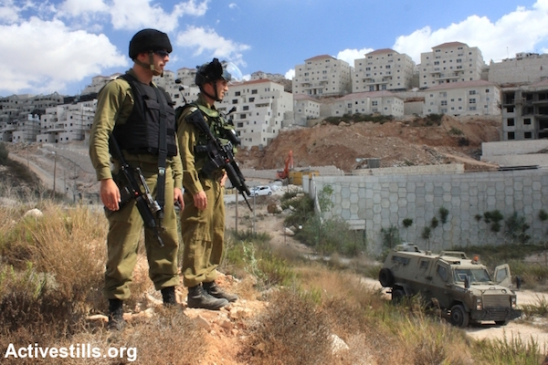 Israeli soldiers stand in front of the West Bank settlement of Beitar Illit, which was partially built on expropriated land belonging to the Palestinian village of Wadi Fukin, West Bank, September 26, 2014. (Ahmad al-Bazz/Activestills.org)