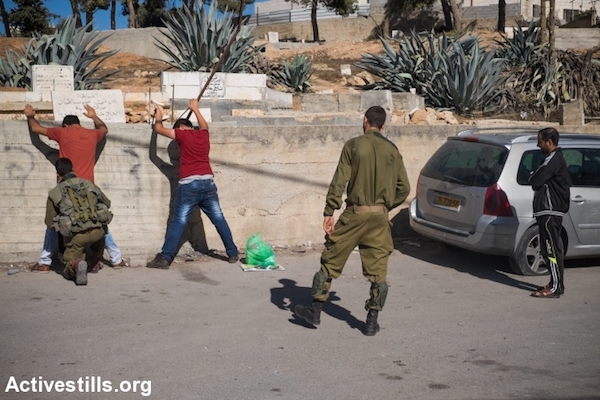 Israeli soldiers search a Palestinian pedestrian in the West Bank city of Hebron, West Bank, October 21, 2015. (Yotam Ronen/Activestills.org) Hebron has seen a disproportionally large part of the violence in recent weeks.