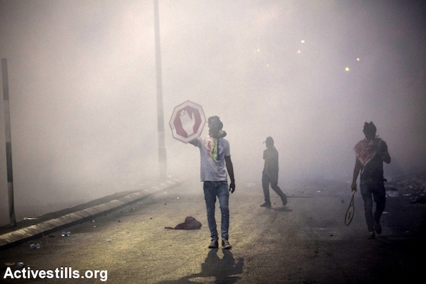 A Palestinian protester uses a stop sign as a shield during clashes with Israeli troops in Bethlehem, West Bank, October 23, 2015. (Anne Paq/Activestills.org)