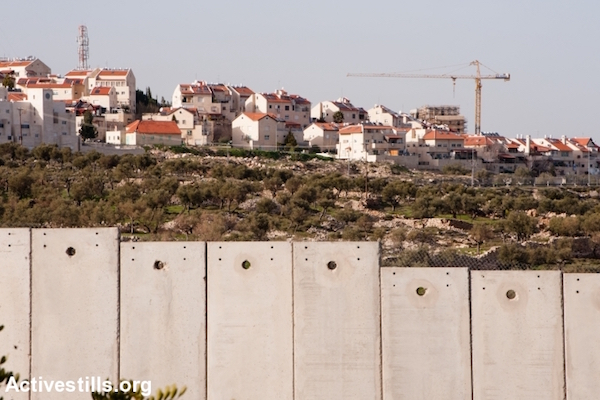 Construction in the Israeli settlement of Gilo is seen over the West Bank separation barrier. (Ryan Rodrick Beiler/Activestills.org)
